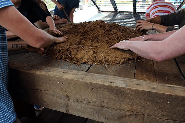 Het maken van de onderplaat van de leemoven, 1e laag met stro